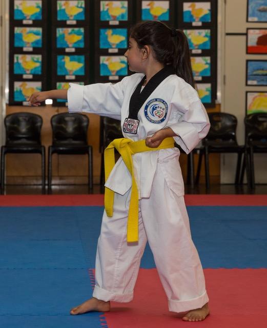 Yellow belt taekwondo student doing a single punch (1)